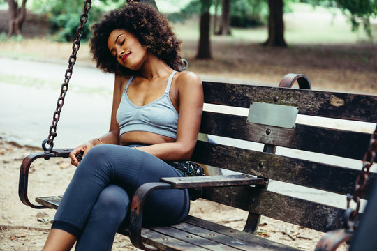 Woman relaxing on park bench swing