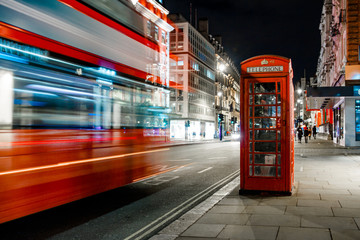Light trails of a double decker bus next to the iconic telephone booth in London Fotomurales