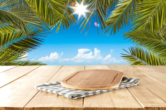 Wooden table background with a cutting board. Blue sunny sky. Palm leaves frame. Blank space for a product.