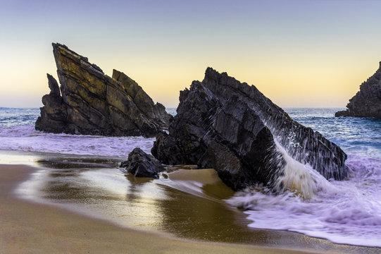 Rocky beach at sunrise, Adraga, Portugal. Travel and business background