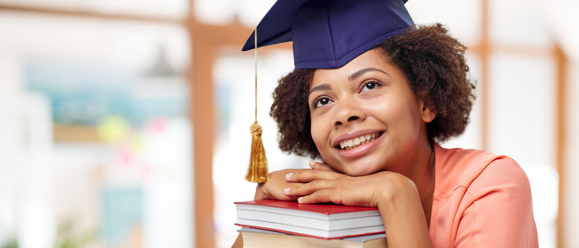 education, graduation and knowledge concept - happy smiling african american graduate student girl in bachelor cap with books dreaming over school background