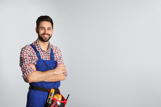 Portrait of construction worker with tool belt on light background. Space for text