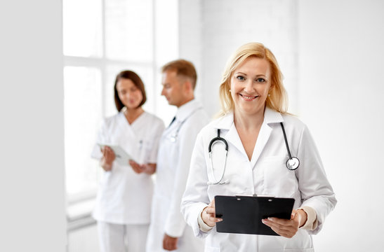 healthcare, medicine and profession concept - smiling female middle aged doctor with clipboard and stethoscope at hospital
