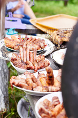 Sausages made on a barbecue lie in the plates, outdoor recreation