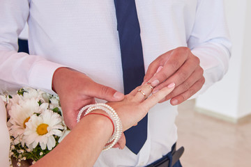 The groom puts the bride ring on the day of their wedding