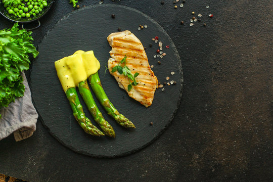 asparagus and chicken grill meat, hollandaise sauce (slate plate). food background. top