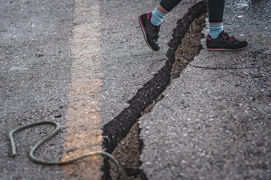 Girl jumping over the crack gap in the road