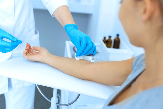 the nurse rubs the hand with alcohol before taking blood from a vein for testing. Disinfects the place of introduction of a needle with antiseptic