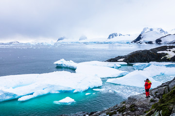Tourist taking photos of amazing frozen landscape in Antarctica with icebergs, snow, mountains and glaciers, beautiful nature in Antarctic Peninsula with ice