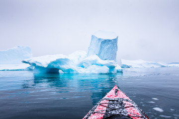 Kayaking between icebergs on a red kayak in Antarctica, POV (point of view) photo with frozen white landscape and blue ice, amazing scene in Antarctic Peninsula, extreme activity