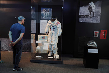 A man looks at an example of space suits used during the Apollo missions at the Cradle of Aviation Museum in Garden City, New York