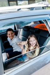 overhead view of happy kid holding wooden biplane near brother in car