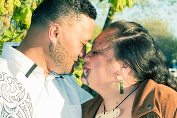 Portrait of an attractive Maori couple connected in a traditional hongi
