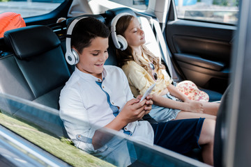 selective focus of boy using smartphone and listening music in headphones near sister with closed eyes in car