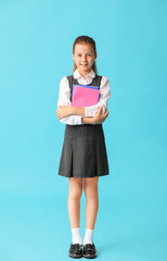 Cute little schoolgirl on color background