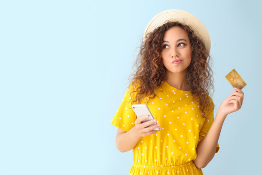 Thoughtful African-American woman with credit card and mobile phone on light color background