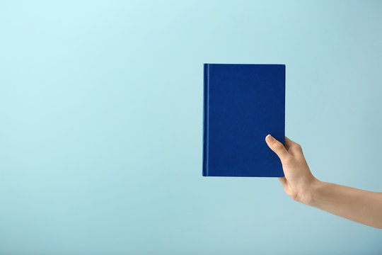Female hand with book on color background