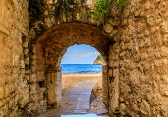 Picturesque brick arch and path of the medieval Old town open onto the Adriatic Sea in the Balkans in Budva, Montenegro Wall mural