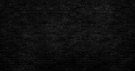 The dark black brick wall has a rough surface as a background image.