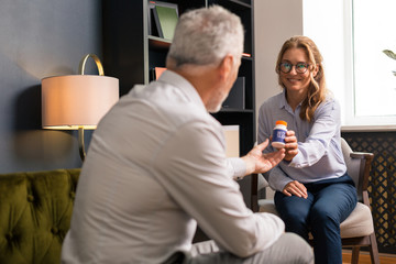 Smiling woman giving her pills to a psychotherapist