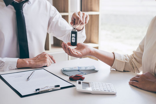 Agent holding key of new car giving to woman client after signing contract