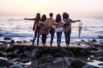 Love and friendship concept with group of female people enjoying the sunset on the ocean together -