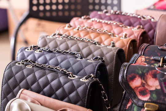 Stylish and trendy leather handbags are seen closeup on the shelf inside a fashion store. Upmarket accessories for classy women.