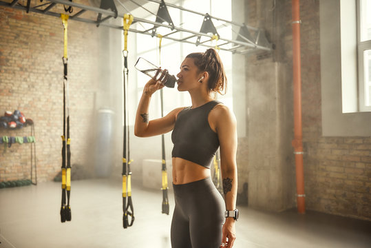 Refreshing. Side view of young athletic woman in earphones with tattoos on her hands is drinking water while exercising in gym.