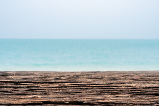 closeup wooden beach bench with sea ocean background, empty product shot with copy space for design