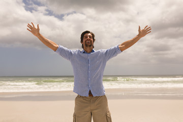 Fototapeta Man standing with arms outstretched on the beach