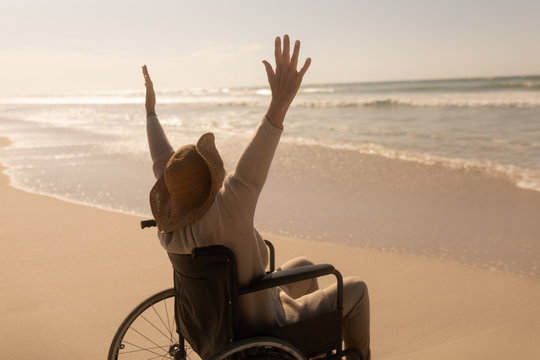 Disabled senior woman with arms up on the beach