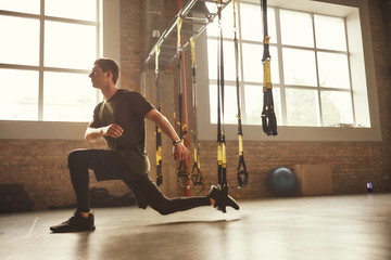 TRX Training. Young athletic man in sports clothing training legs with trx fitness straps in the gym