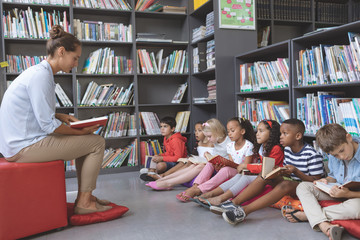 Teacher reading a story to school kids holding a book to follow her