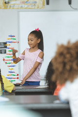 Mixed-race ethnicity schoolgirl analyzing DNA structure model at school