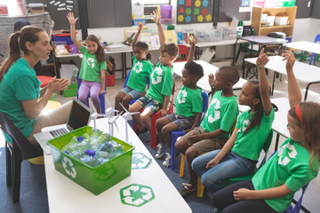 School kids wearing recycle tee-shirt raising hand to answer at a question