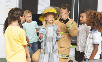 Firefighter teaching student about fire safety in classroom