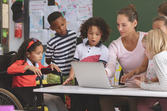 Teacher and school kids discussing over laptop in classroom