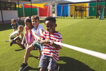 Fototapeta Group of school kids playing tug of war obraz