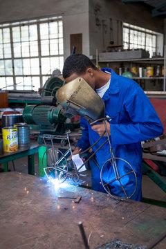 Students welding in a workshop. Boy welding a bike out of metal wire.