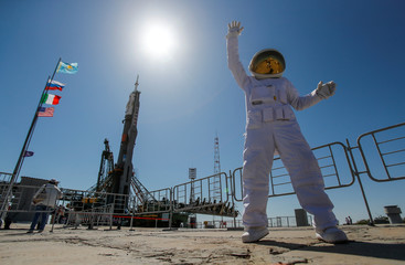 A man dressed in a cosmonaut costume poses for media in front of Soyuz MS-13 spacecraft for the new International Space Station (ISS) crew installed at the launchpad ahead of its upcoming launch, at the Baikonur Cosmodrome