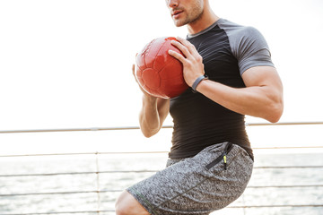 Strong young sports man outdoors make exercises with ball.