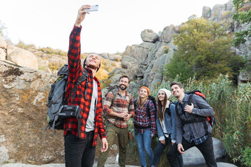 Group of friends outside in free alternative vacation camping take a selfie by phone.