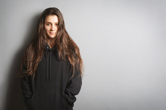 cool young woman with long brunette hair wearing black hoodie sweater leaning against wall with her hands in pockets - gray background with copy space