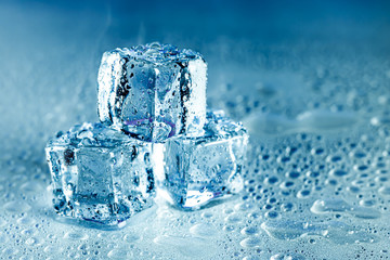 Ice cubes and water melt on cool background. Ice blocks with cold drinks or beverage.