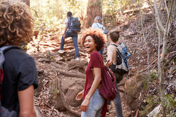 Group of millennial  friends hiking uphill on a forest trail, three quarter length Fotobehang