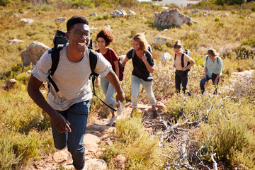 Millennial African American man leading friends hiking single file uphill on a path in countryside Fotobehang