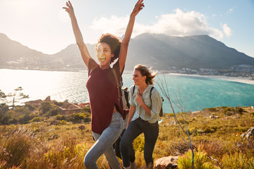 Millennial African American woman hiking by the coast with a friend celebrates reaching summit Wall mural