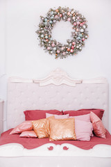 Classic bedroom interior in the New Year's style. Christmas wreath over the bed