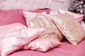 pink pillows lie on the bed, in the background a Christmas tree