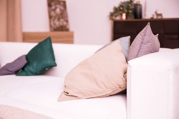 pillows lie on a bright sofa in the room with New Year decorations